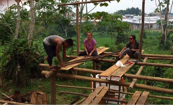 Nina and Gabby helping Vinnie build the kitchen maloka's roof.